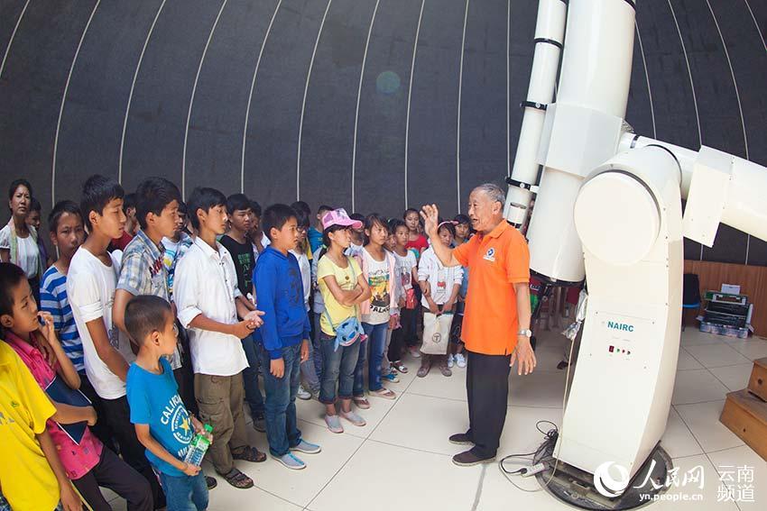 天文学专家在墨江北回归线标志园天文馆给学生讲解天文望远镜的原理。(人民网 李发兴 摄)