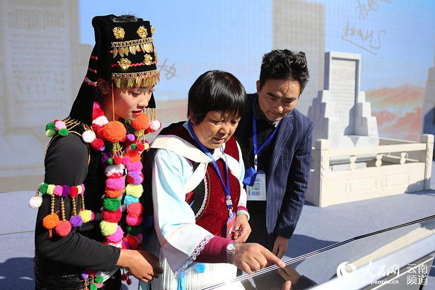 1月19日,参加主题活动的代表在续写民族团结誓词碑。(人民网 李发兴 摄)