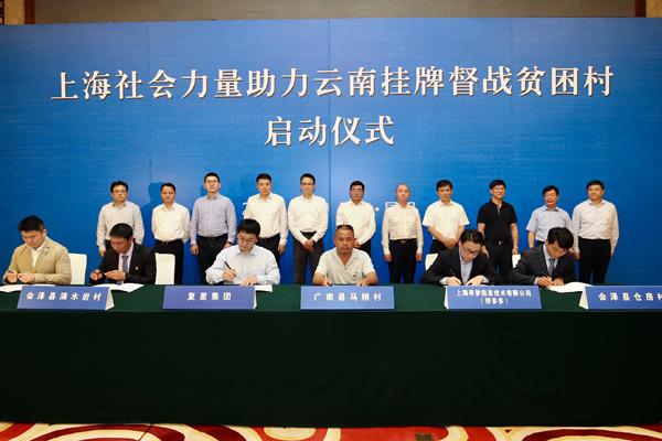 """上海市企业代表与""""挂牌督战村""""代表签约。(吴名 摄)"""